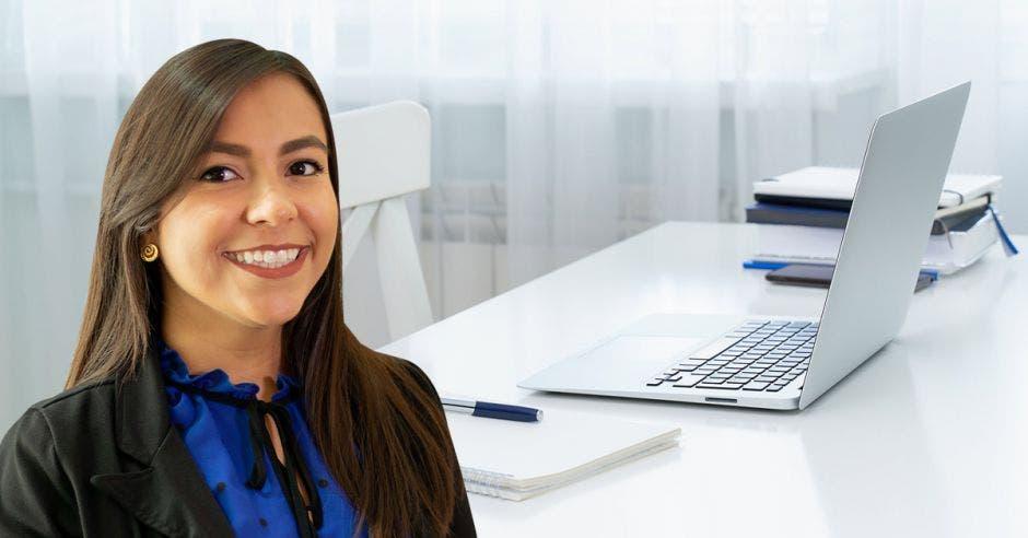 Un mujer posa junto a un escritorio y una computadora