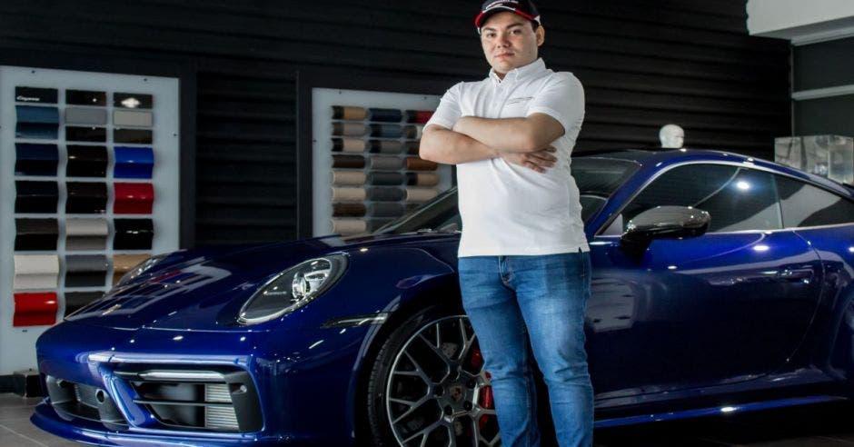 Hombre posa frente a un auto Porsche