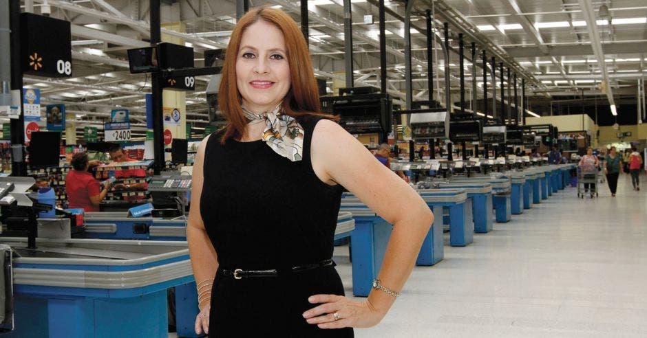 Mujer posa frente a cajas de supermercado