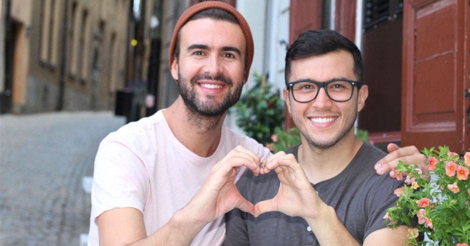 Pareja homosexual hace un corazón juntando sus manos