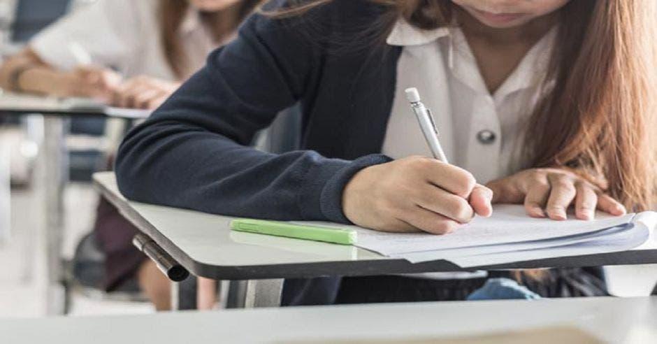 Joven escribiendo y tomando nota durante clases