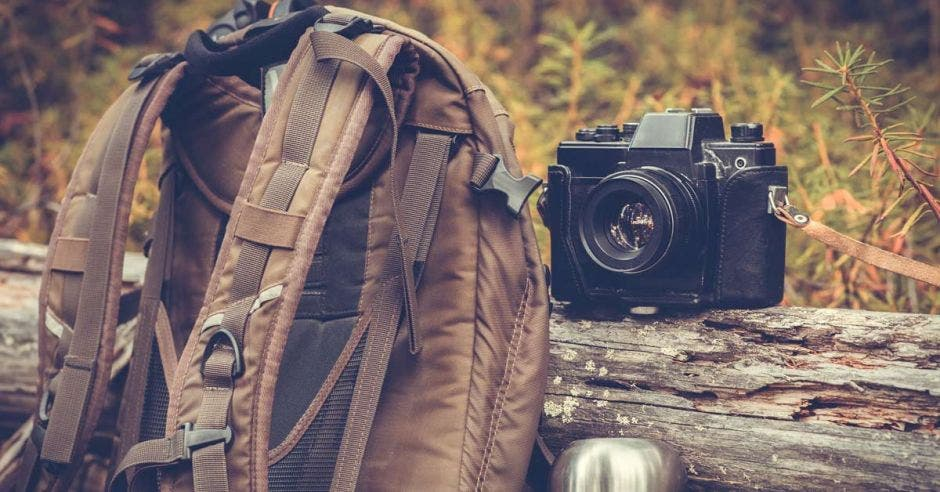 Una mochila, una cámara fotográfica y un termo de aluminio con café