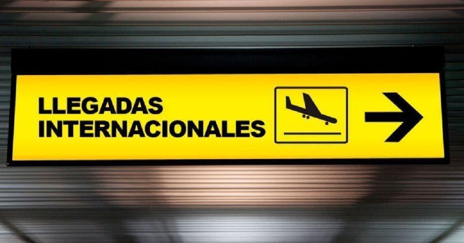 Aeropuerto con una señal de dirección de salida de las llegadas internacionales