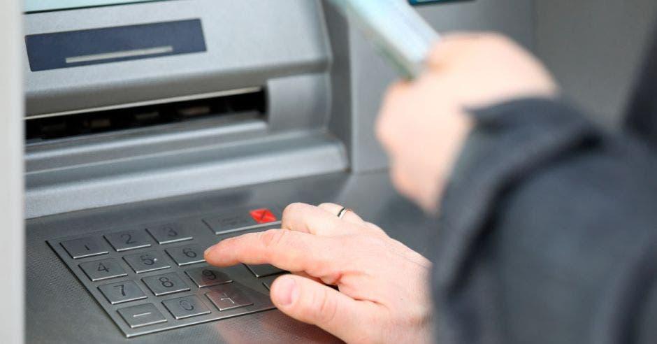 Persona adulta mayor sacando dinero de cajero automático