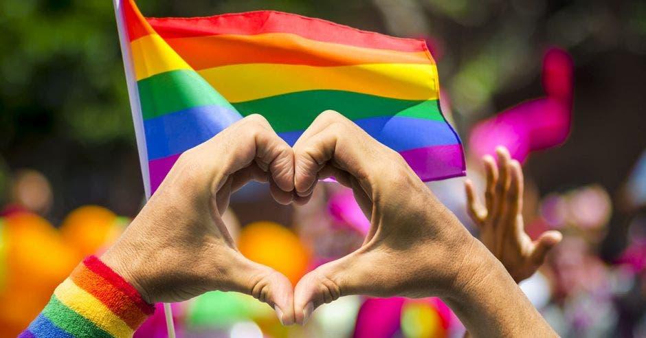 Bandera de la diversidad y persona haciendo símbolo de corazón