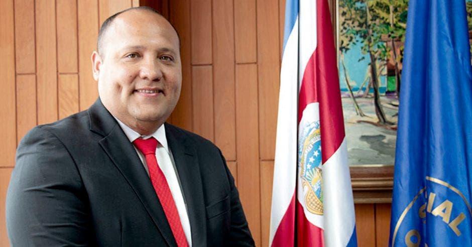 Un hombre posa junto a dos banderas, una de costa rica y otra color azul con el logo de la CCSS