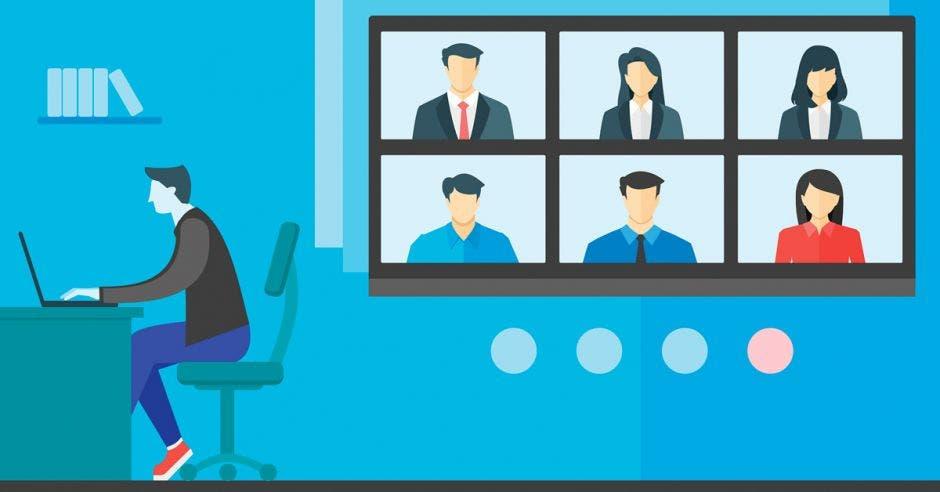 Hombre sentado en escritorio escribe junto a varias pantallas con otros trabajadores en medio de una reunión
