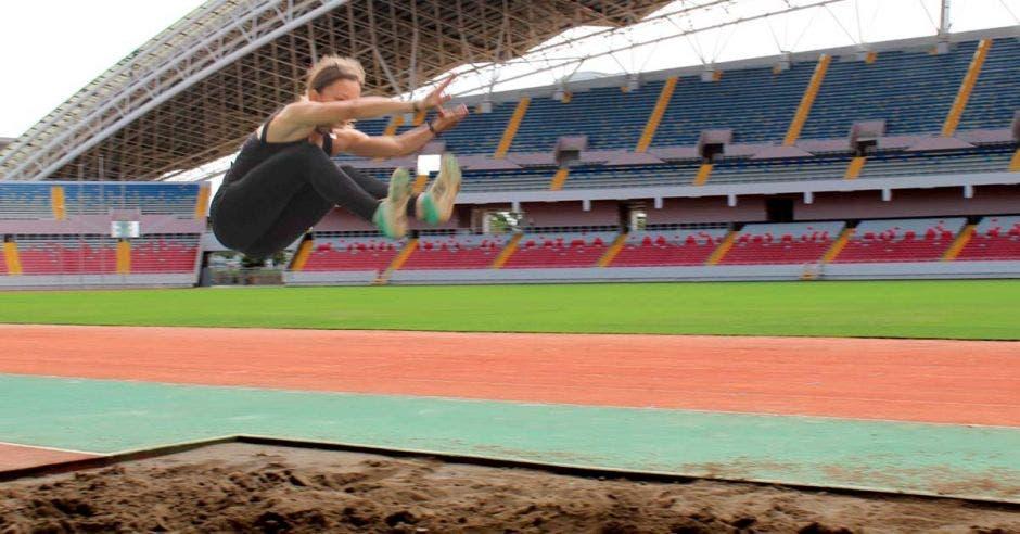 Persona haciendo salto largo en el estadio nacional