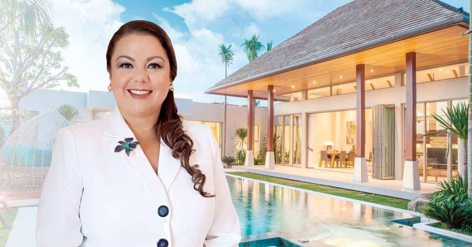 Mujer posa frente a casa de lujo