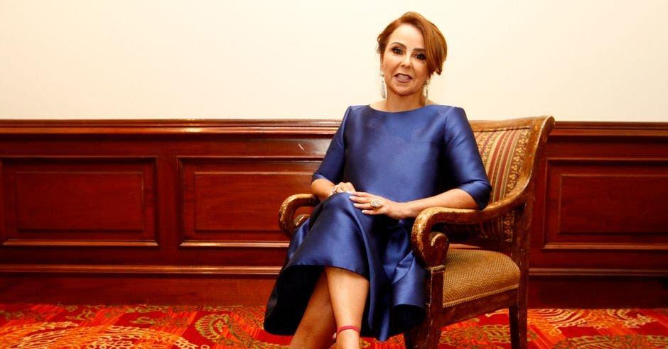Una mujer con vestido azul sentada en una silla elegante