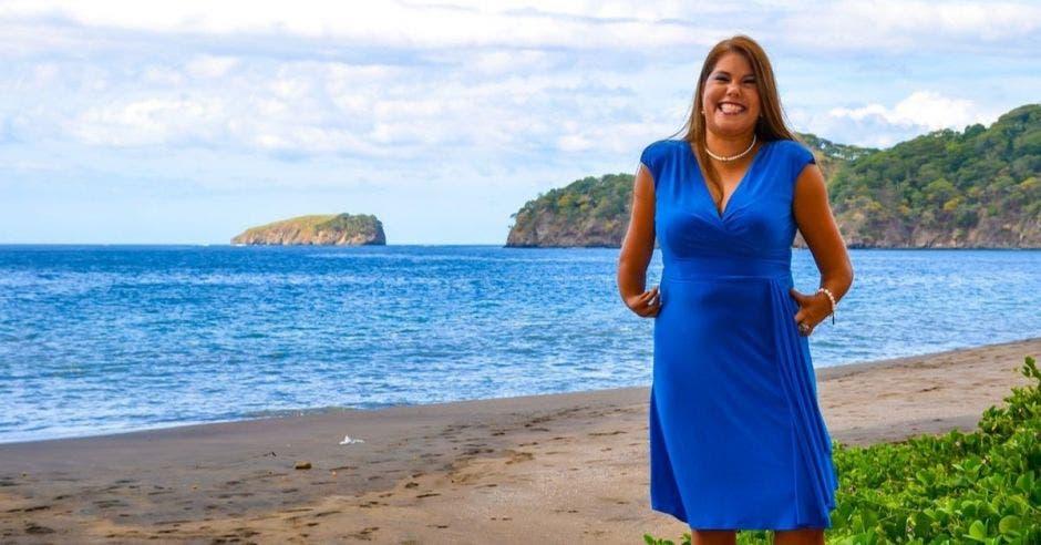 Una mujer con vestido azul posa en la playa