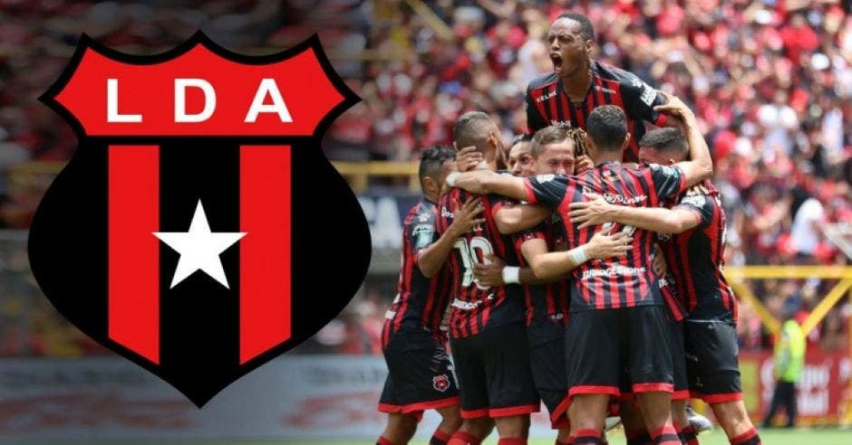 Jugadores de fútbol celebrando un gol con el escudo de Alajuelense de fondo