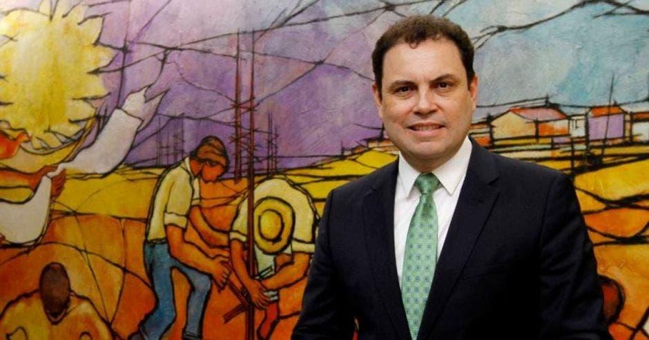 Carlos Ricardo Benavides, diputado de Liberación, posa para una fotografía con una pintura de fondo
