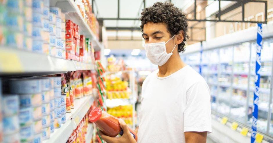 Un hombre con mascarilla compra salsa de tomate en el supermercado