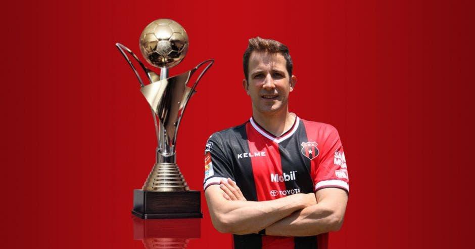 Hombre de brazos cruzados posa frente a un trofeo