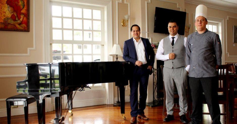 tres hombres posan junto a un piano