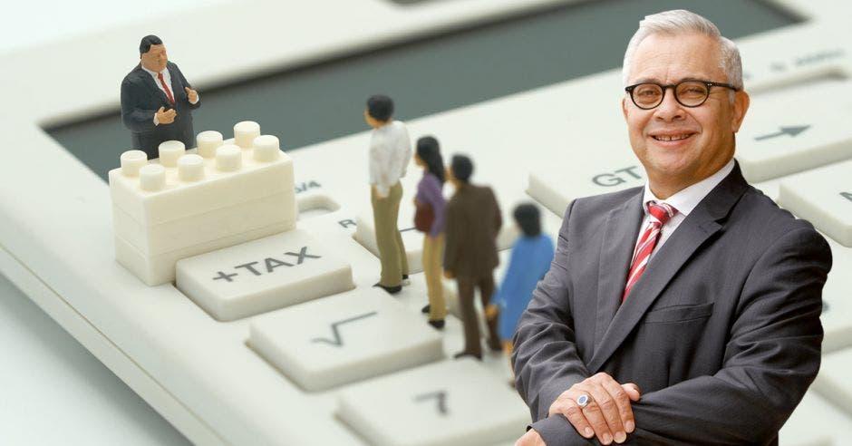 Carlos Camacho con personas de fondo haciendo fila en una calculadora
