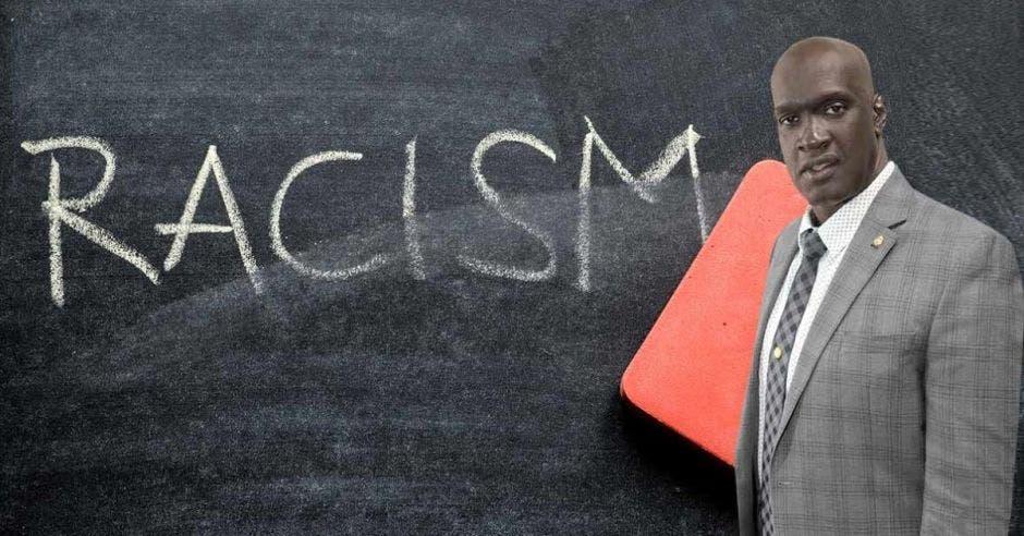 Eduardo Cruickshank con fondo de una pizarra con racismo escrito en tiza