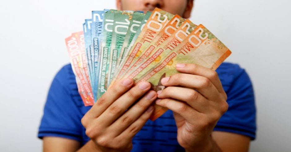 Hombre sostiene una variedad de billetes