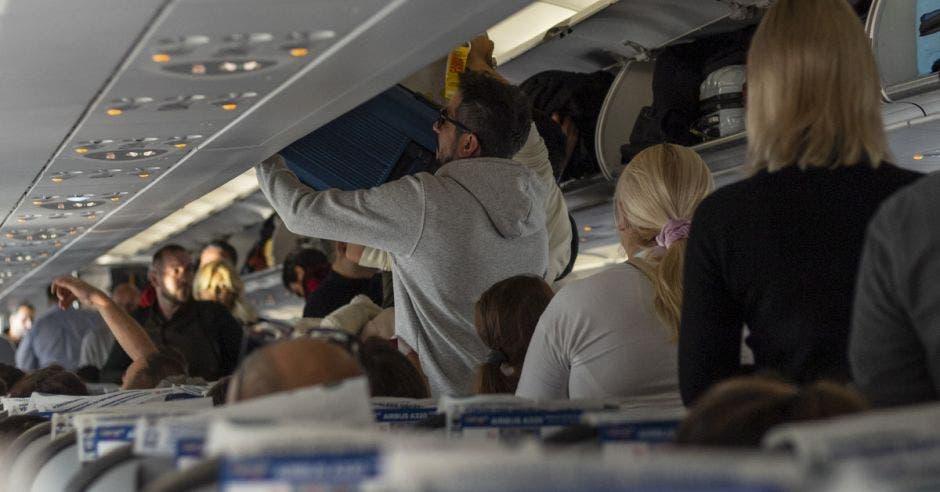 Pasajeros de avión colocan sus valijas