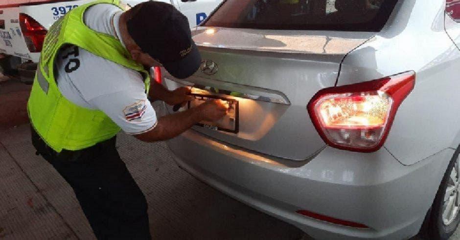 Oficial de tránsito aplicando el retiro de placas en un vehiculo