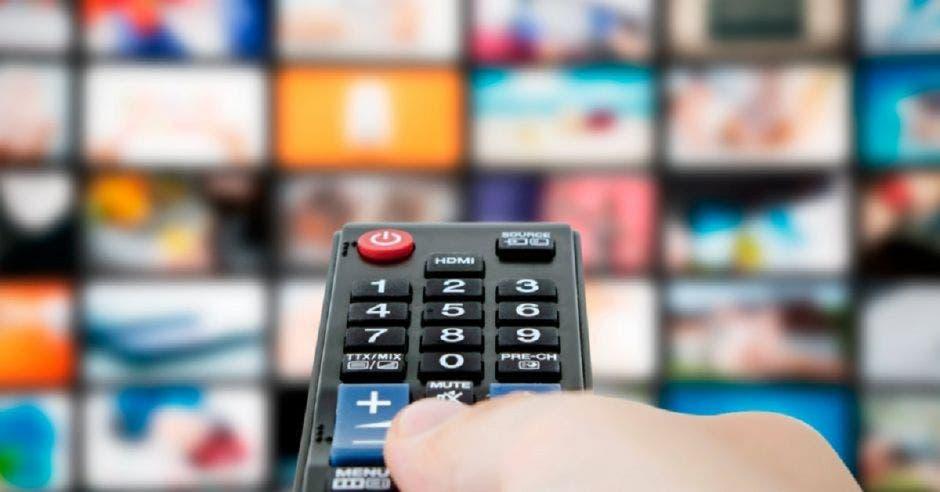 Mano con un control apunta a varias pantallas de streaming