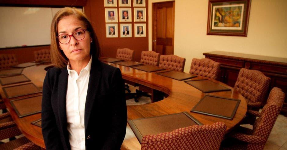 Mujer de lentes posa en una sala de reuniones con la mesa de fondo