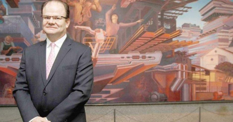 Elián Villegas, titular de Hacienda posa frente a una pintura