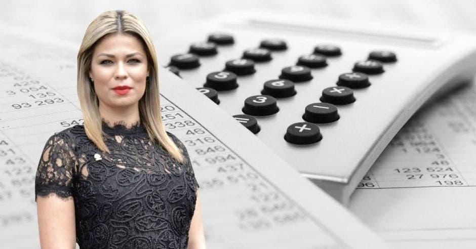 Mujer posa con una calculadora de fondo