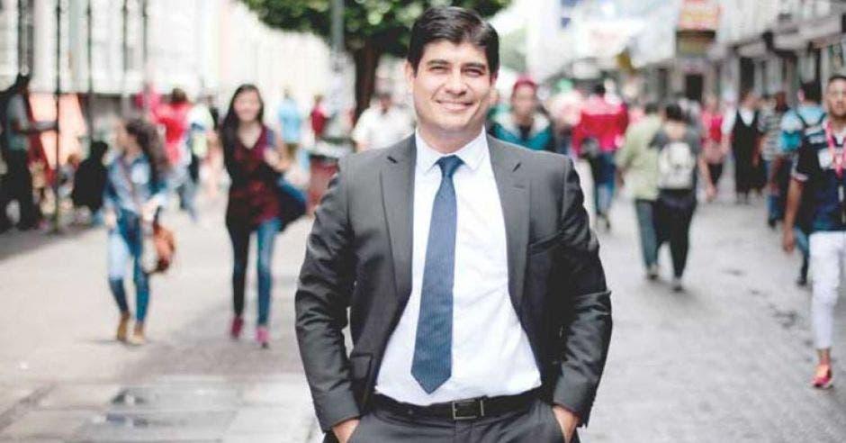 Carlos Alvarado vestido de traje en el medio de San José