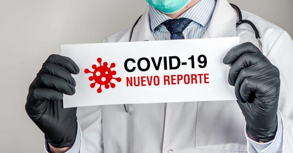 Hombre con bata y guantes sostiene papel con casos de Covid-19