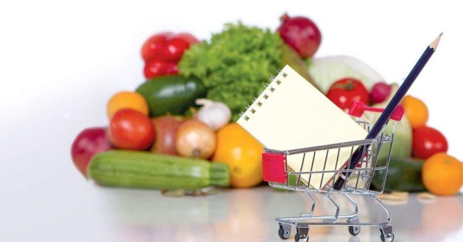 Múltiples frutas y vegetales con un carrito de supermercado y un bolígrafo