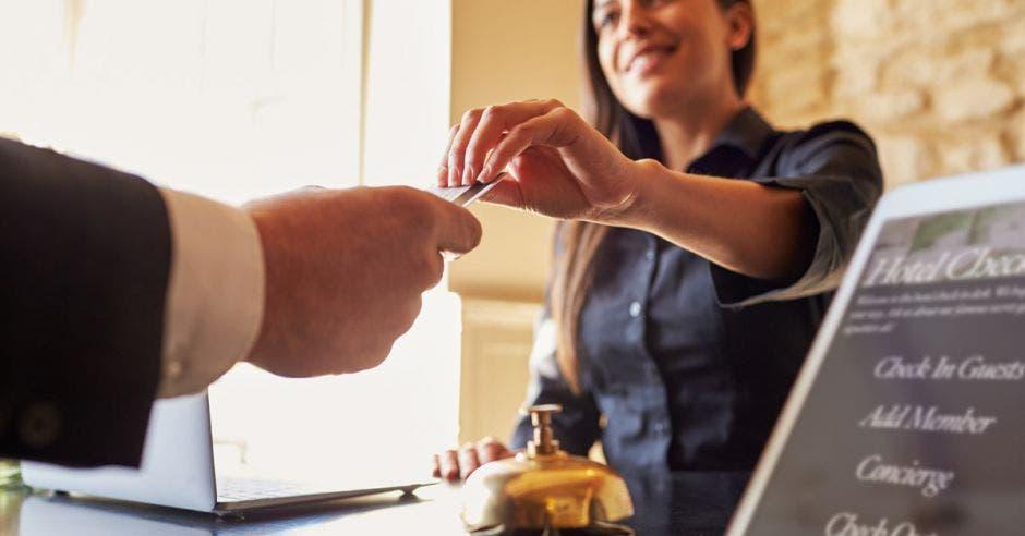 Una dependiente de hotel entrega unas llaves a un huésped