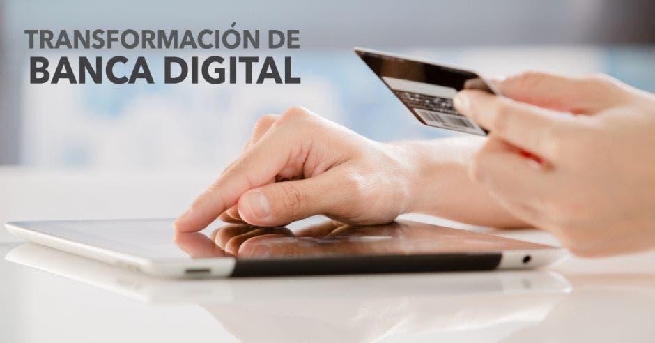 Persona tiene en una mano una tarjeta y con la otra digita en una tableta