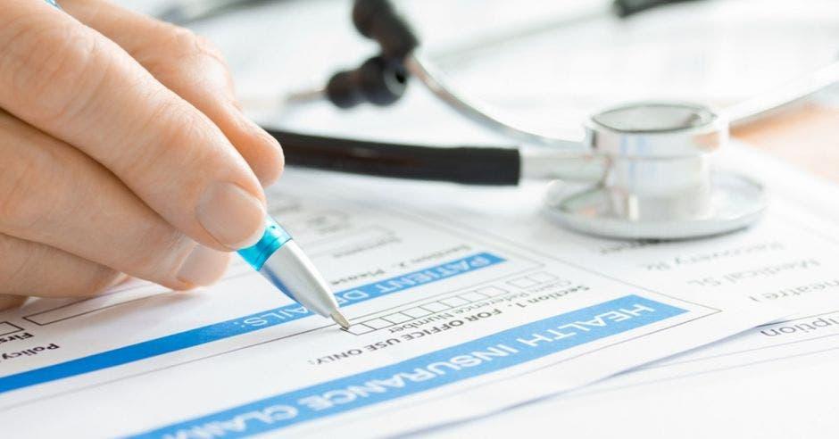 Persona con bolígrafo escribe en papel y estetoscopio