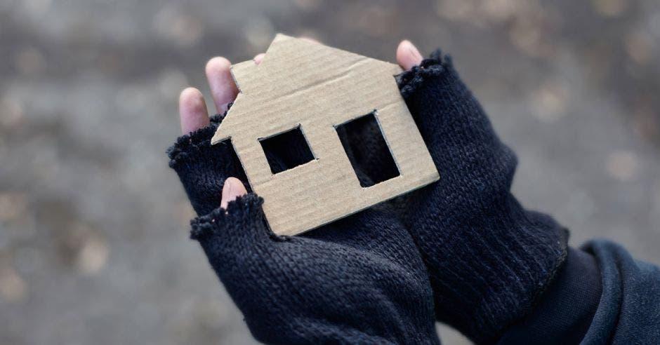 Una persona sin techo con una figura de casa hecha de cartón