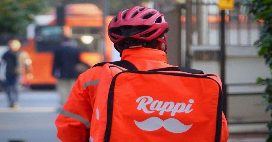 Hombre con casco y moto laborando en Rappi