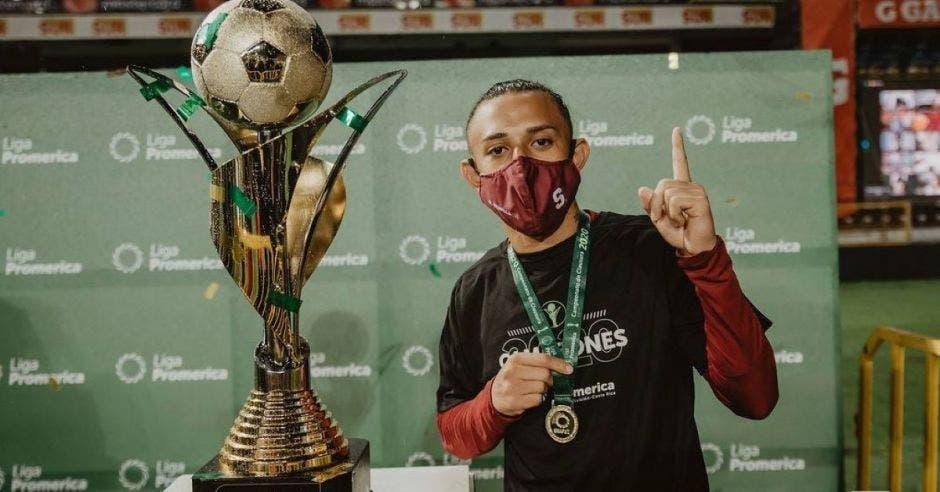 Jugador portando medalla posa junto a un trofeo