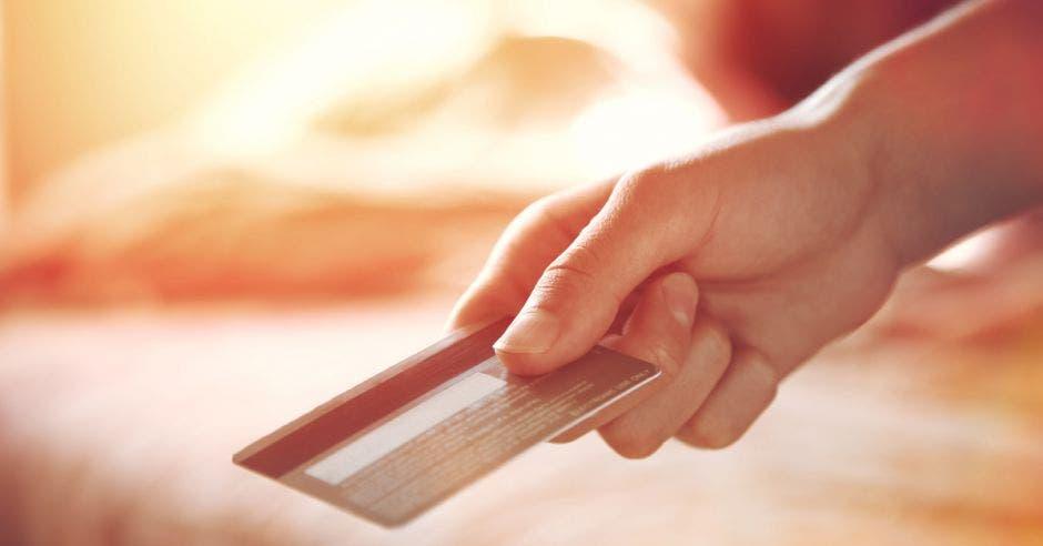 Mano entregando una tarjeta de crédito