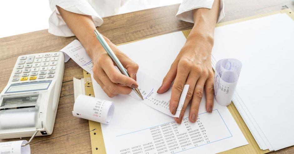 Mujer saca facturas, bolígrafo y calculadora