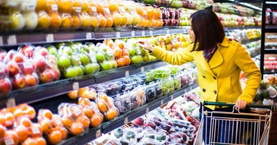 Mujer con carrito de supermercado escoge frutas