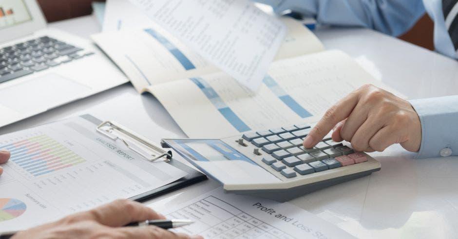 Vemos varios papeles puestos y una calculadora la cual está siendo utilizada por una mano.