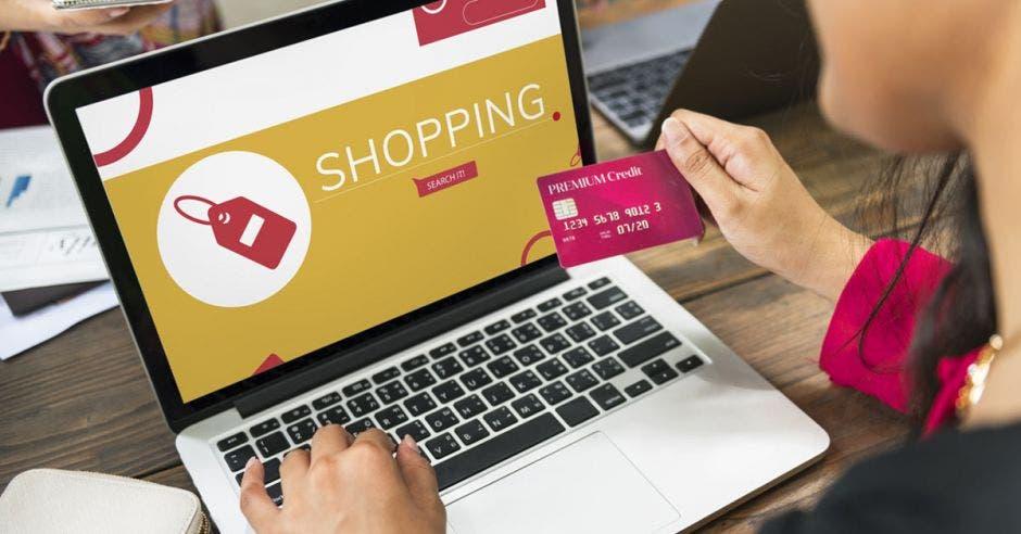Viendo tarjeta de crédito una mujer mientras entra en un sitio online