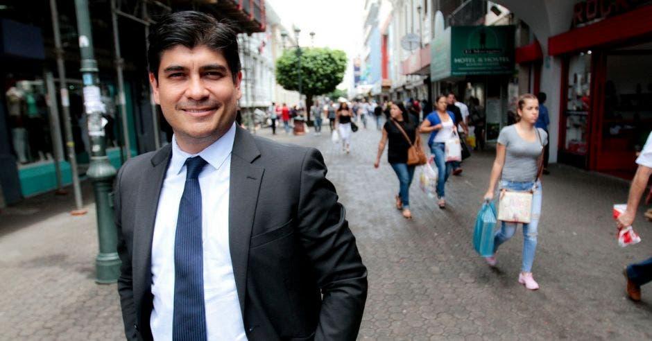 Carlos Alvarado en medio San José con personas pasando