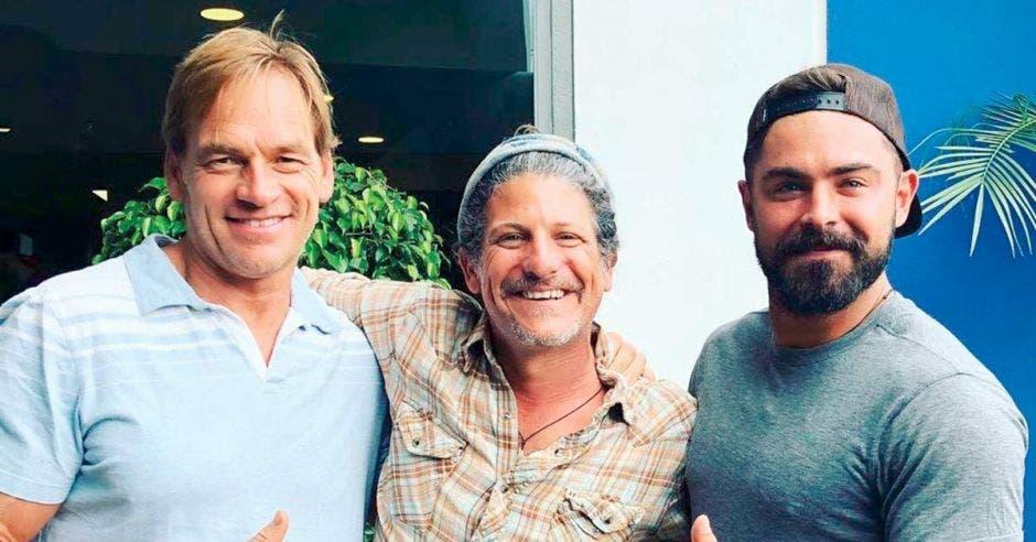 Tres hombres caucásicos sonríen abrazados