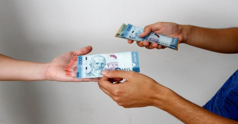 Persona le da a otra billetes en la mano