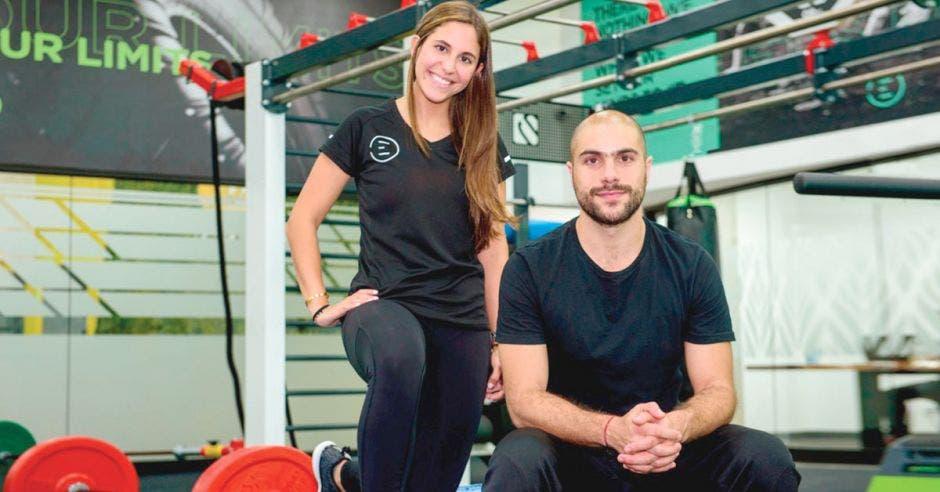 Dos personas, una de pie y otra sentada en gimnasio