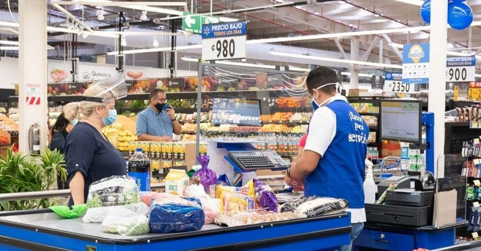 Un cajero atiende a una mujer desde el mostrador de un supermercado