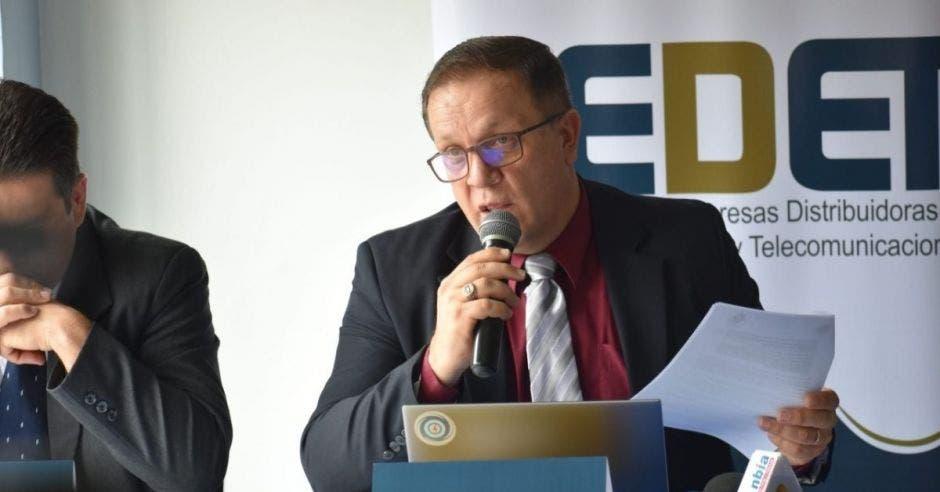 Un hombre en traje oscuro y corbata plateada se dirige a una audiencia con un micrófono