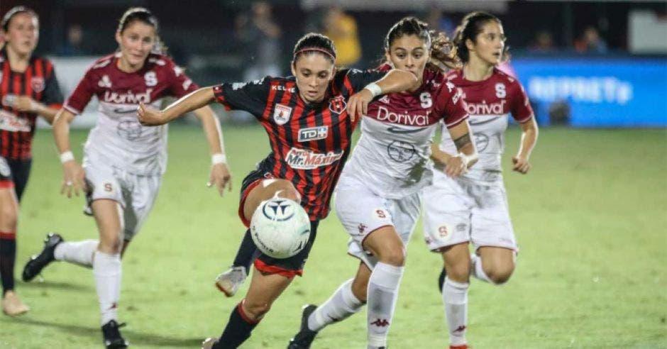 futbol femenino jugándose con dos mujeres disputando un balón